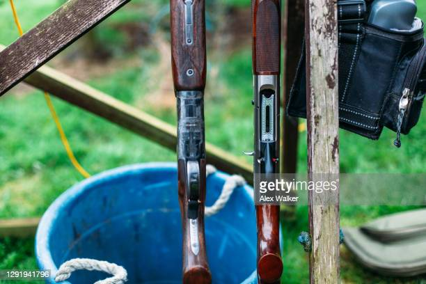 close up of two shotguns in a rack with shell bag hanging. - shooting crime stock pictures, royalty-free photos & images
