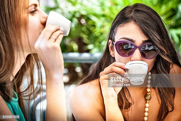 Close up of two young female friends drinking espresso at sidewalk cafe, Cagliari, Sardinia, Italy