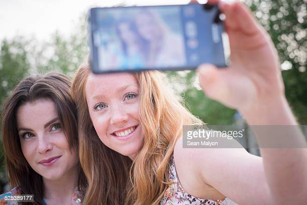 close up of two young female friends in park taking selfie on smartphone - sean malyon stock pictures, royalty-free photos & images