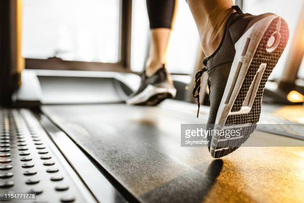 close up of unrecognizable athlete running on a treadmill in a gym. - athleticism stock pictures, royalty-free photos & images