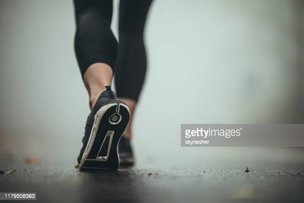 close up of unrecognizable athlete walking during foggy day. - human foot stock pictures, royalty-free photos & images