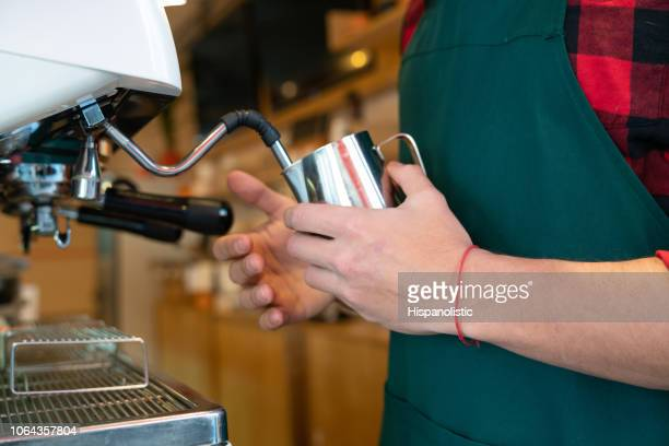 close up of unrecognizable barista making a capucchino with the machine - hispanolistic stock photos and pictures