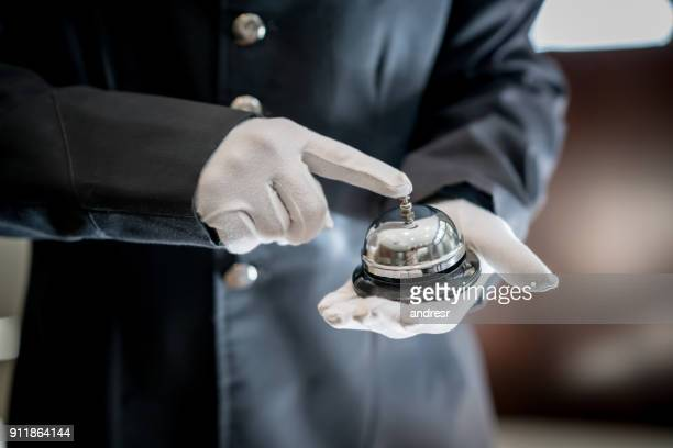 Close up of unrecognizable bell boy at a hotel ringing the bell