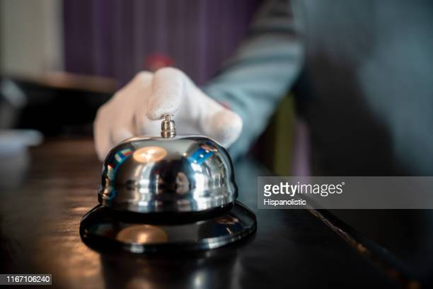 close up of unrecognizable bellhop ringing a bell on hotel check in counter - hotel stock pictures, royalty-free photos & images