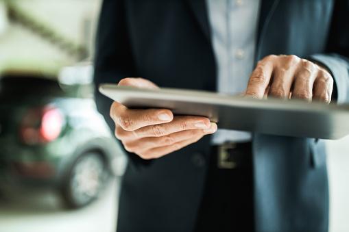 Close up of unrecognizable car salesman using digital tablet. 1174844182