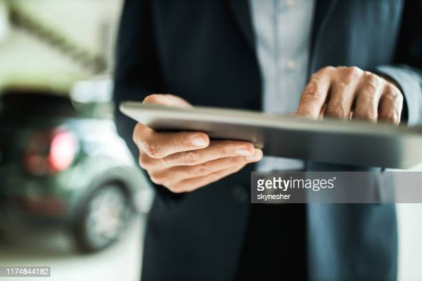 close up of unrecognizable car salesman using digital tablet. - touchpad stock pictures, royalty-free photos & images