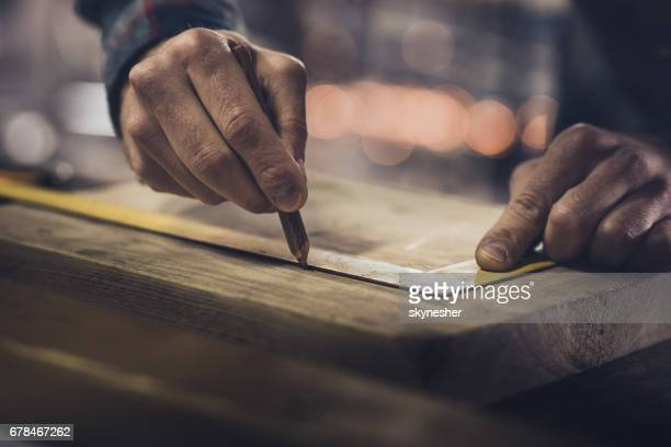 close up of unrecognizable carpenter drawing measurements on a wood. - craftsman stock photos and pictures