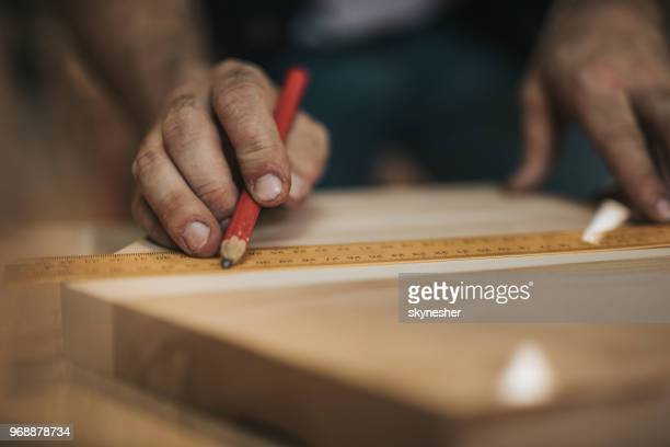 Close up of unrecognizable carpenter drawing measurements on a wood.