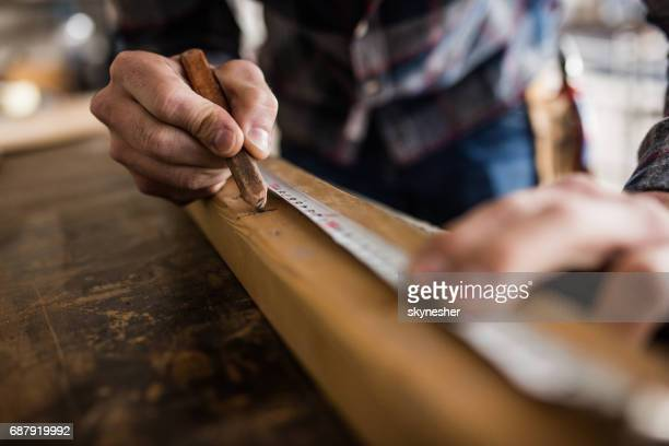 close up of unrecognizable carpenter marking measurements on a piece of wood. - medir imagens e fotografias de stock