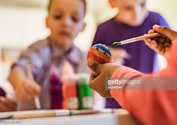 close up of unrecognizable child coloring easter egg. - african american easter stock photos and pictures