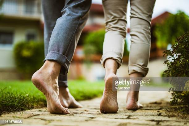 close up of unrecognizable couple walking barefoot in the backyard. - barefoot stock pictures, royalty-free photos & images