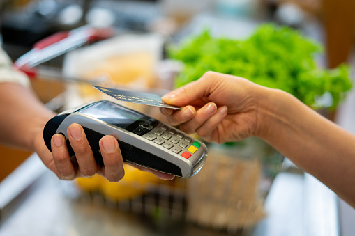 Close up of unrecognizable customer doing a contactless payment at the supermarket 1128053940