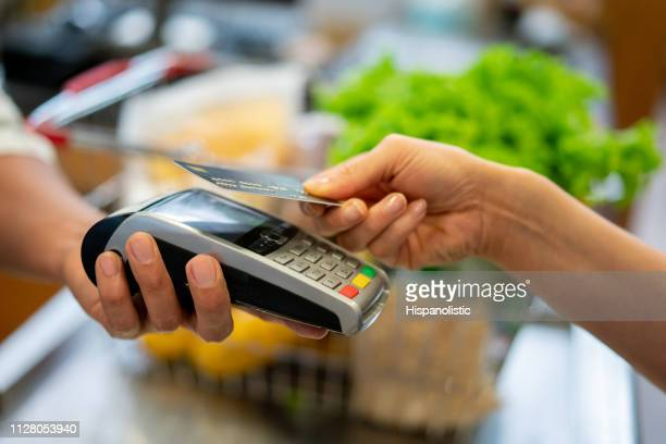 close up of unrecognizable customer doing a contactless payment at the supermarket - credit card reader stock pictures, royalty-free photos & images