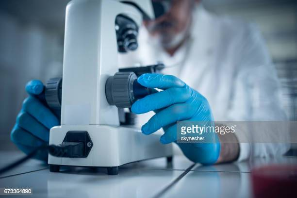 Close up of unrecognizable doctor using a microscope.