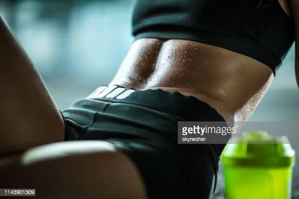 nahaufnahme von nicht erkennbaren weiblichen athleten mit verschwitzten bauchmuskeln. - muskel stock-fotos und bilder