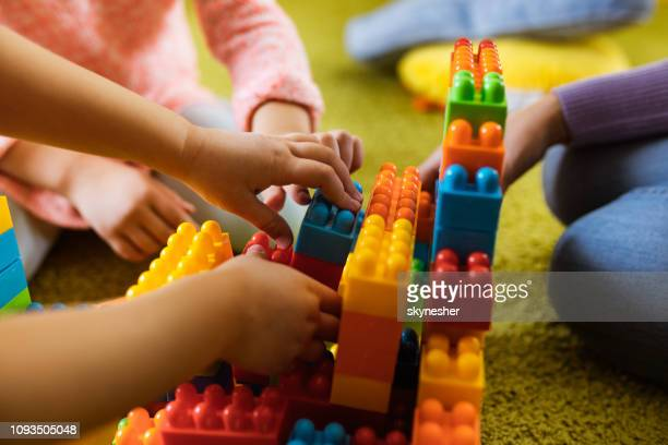 close up of unrecognizable kids playing with toy blocks on carpet. - preschool stock pictures, royalty-free photos & images