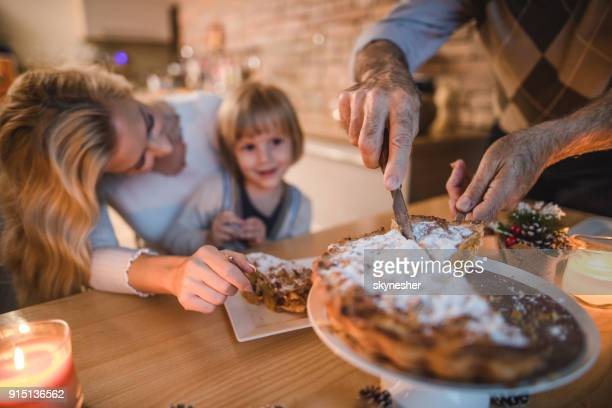 Close up of unrecognizable man cutting apple pie during meal with his family.