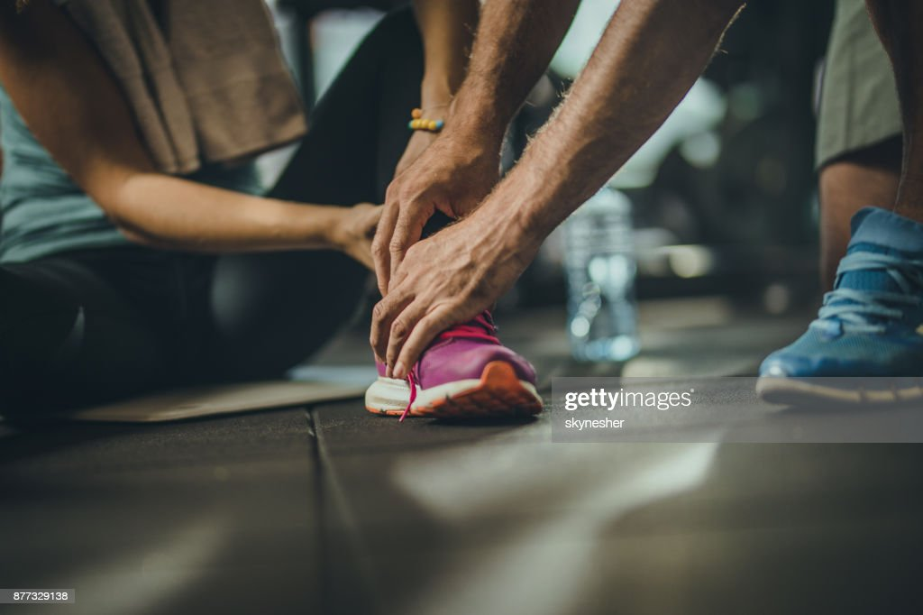 Close up of unrecognizable man helping injured sportswoman in a gym. : Stock Photo
