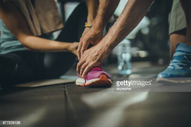 close up of unrecognizable man helping injured sportswoman in a gym. - sprain stock pictures, royalty-free photos & images