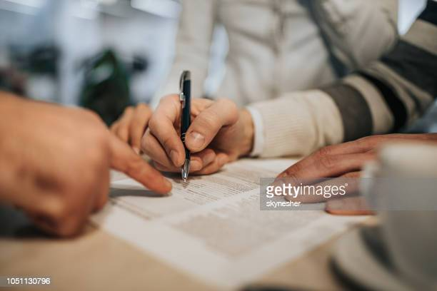 close up of unrecognizable man signing a contract. - life insurance stock pictures, royalty-free photos & images