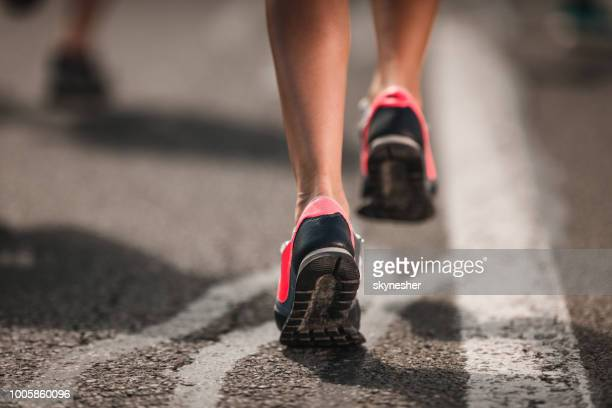 Close up of unrecognizable marathon runner in motion on the road.