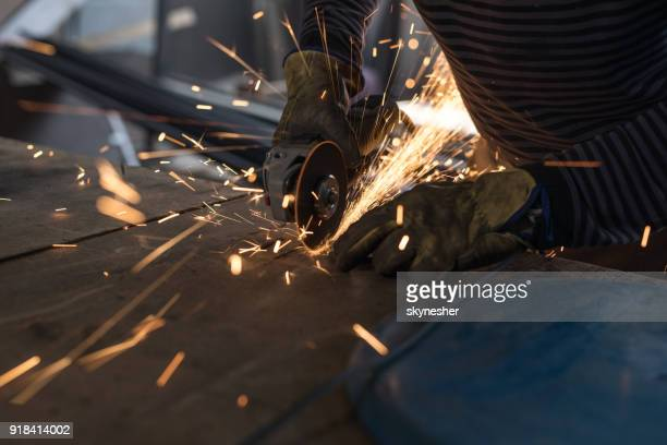 Close up of unrecognizable metal worker grinding metal with an electric saw.