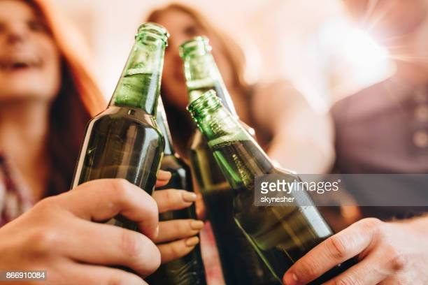 Close up of unrecognizable people toasting with beer.