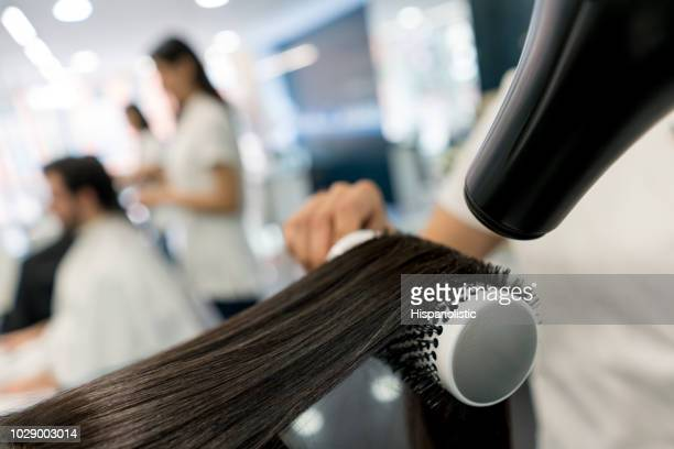 Close up of unrecognizable person blow drying a customers hair using a brush