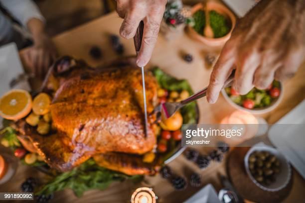 gros personne méconnaissable, viande blanche de sculpture au cours du dîner de thanksgiving à table à manger. - viande blanche photos et images de collection