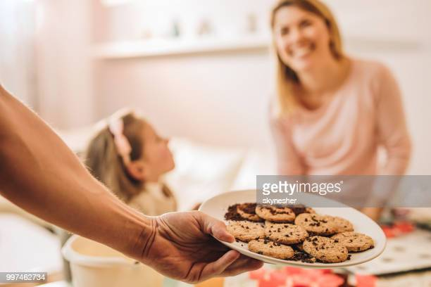 Close up of unrecognizable person holding chocolate chip cookies on a plate.