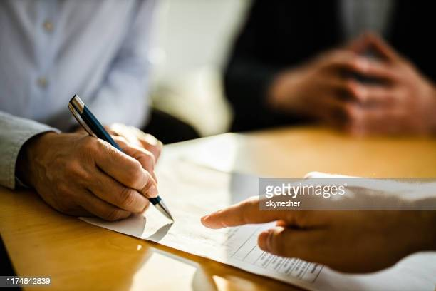 close up of unrecognizable person signing a contract. - form filling stock pictures, royalty-free photos & images