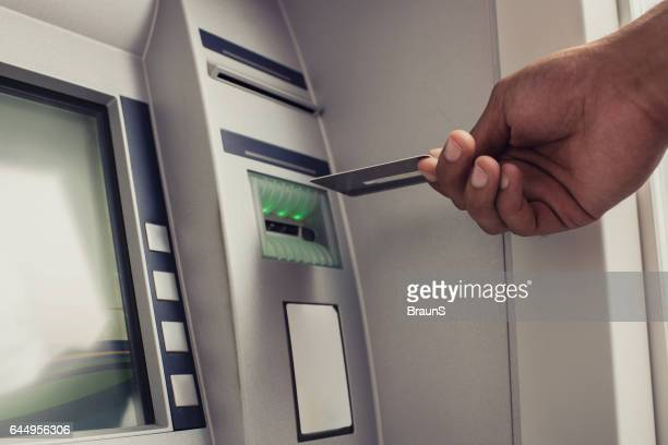 Close up van onherkenbaar persoon met credit card over ATM.