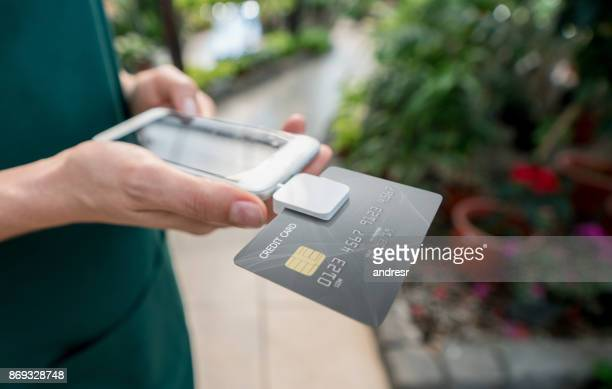 close up of unrecognizable saleswoman doing the checkout using a credit card reader and smartphone - credit card reader stock pictures, royalty-free photos & images