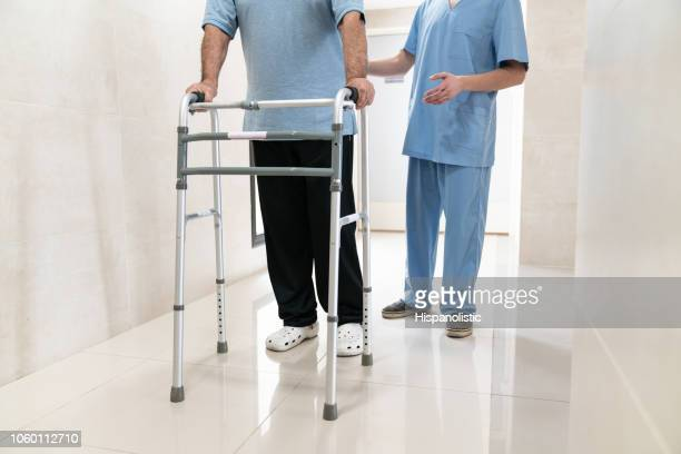 close up of unrecognizable senior adult using a walker and nurse behind him - crutches stock photos and pictures