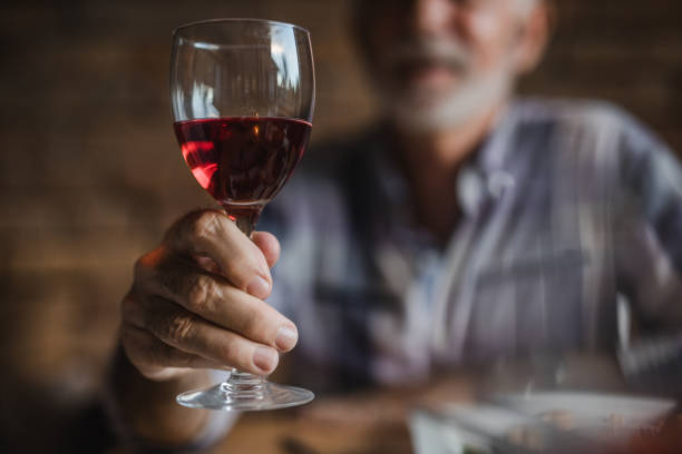 close up of unrecognizable senior man holding glass of red wine. - red wine sip stock pictures, royalty-free photos & images
