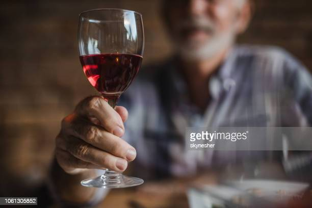close up of unrecognizable senior man holding glass of red wine. - alcohol drink stock pictures, royalty-free photos & images