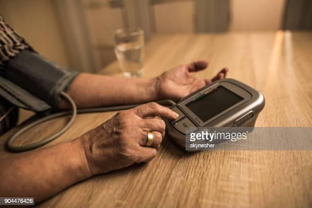 Nahaufnahme von unkenntlich ältere Frau, die ihren Blutdruck zu Hause messen.