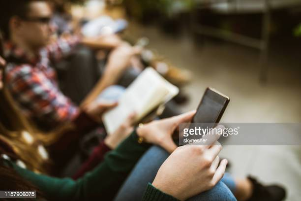 close up of unrecognizable student using cell phone in a hallway. - building feature stock pictures, royalty-free photos & images