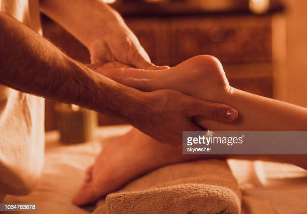 close up of unrecognizable therapist massaging customer's foot at health spa. - foot massage stock pictures, royalty-free photos & images
