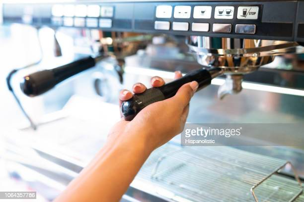 close up of unrecognizable waitress using the coffee machine - hispanolistic stock photos and pictures
