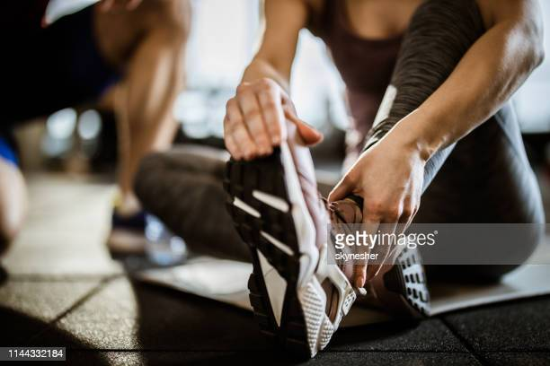 close up of unrecognizable woman feeling pain in her ankle at gym. - sprain stock pictures, royalty-free photos & images