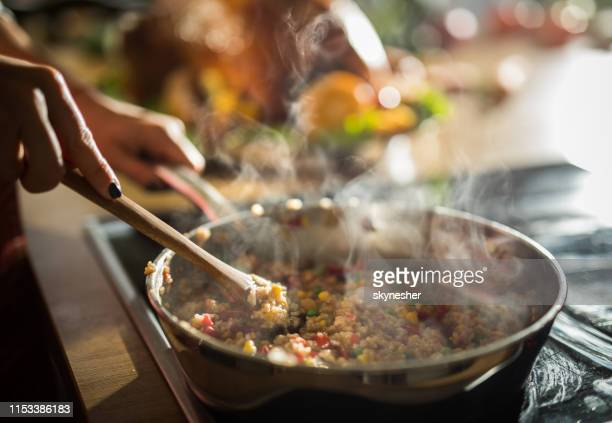 close up of unrecognizable woman preparing lunch in the kitchen. - frying pan stock pictures, royalty-free photos & images