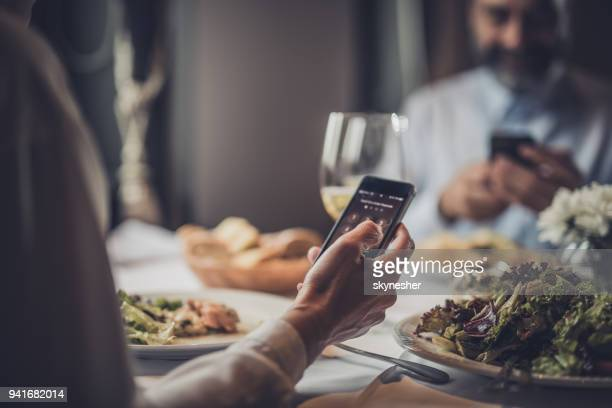 Close up of unrecognizable woman using mobile phone in a restaurant.