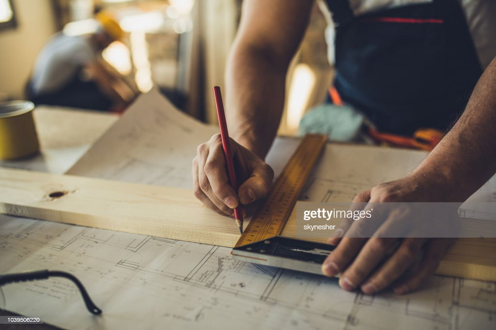 Close up of unrecognizable worker drawing on wood plank. : Stock Photo