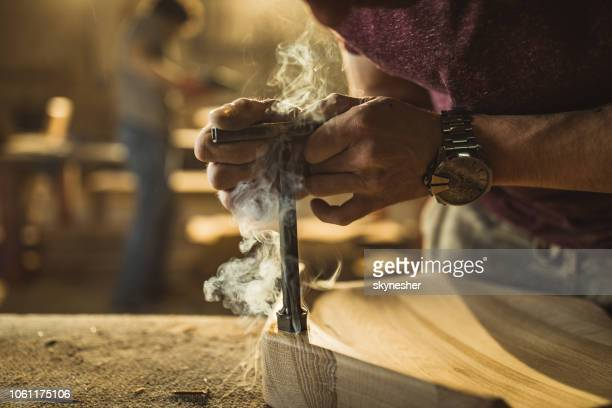 close up of unrecognizable worker imprinting the logo on the wood. - logo design stock photos and pictures