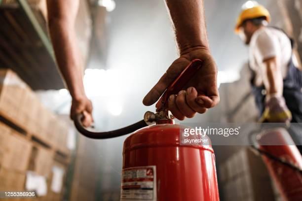 倉庫で消火器を使用してクローズアップ。 - 消火器 ストックフォトと画像