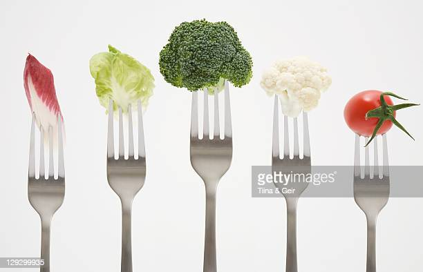close up of vegetables on forks - forchetta foto e immagini stock