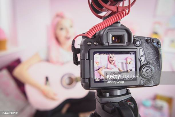 Close up of video camera viewfinder with young woman playing guitar