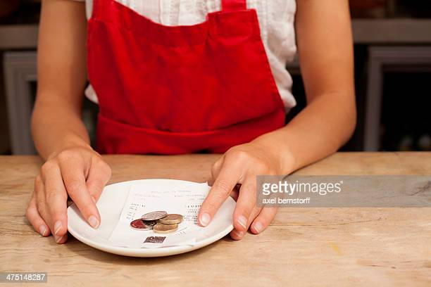 close up of waitress with bill and gratuity at kitchen counter - silver blouse stock pictures, royalty-free photos & images