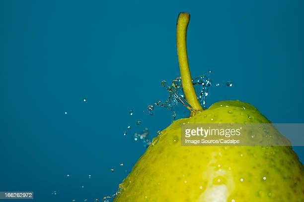 Close up of water splashing on pear